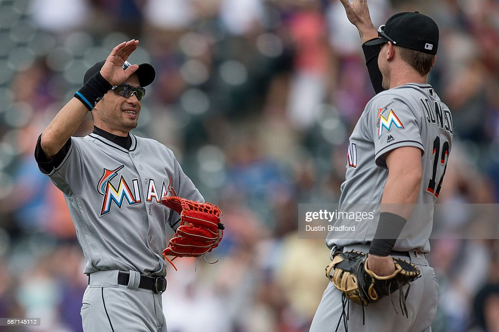 Ichiro Suzuki of the Miami Marlins celebrates a 107 win over the Colorado Rockies with Chris Johnson after a game at Coors Field on August 7 2016 in...