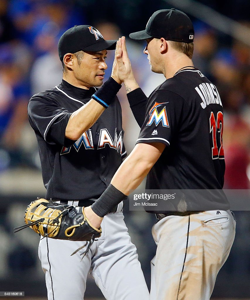 Ichiro Suzuki of the Miami Marlins celebrates with teammate Chris Johnson after defeating the New York Mets at Citi Field on July 5 2016 in the...