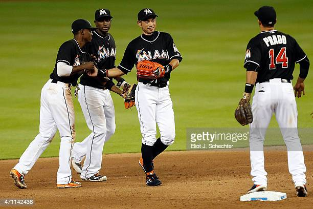 Ichiro Suzuki of the Miami Marlins celebrates with teammates after breaking the record for the most runs scored by a Japanese player and their win...