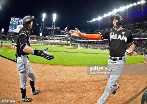 Ichiro Suzuki of the Miami Marlins congratulates Giancarlo Stanton after scoring a ninth inning run against the Atlanta Braves at SunTrust Park on...