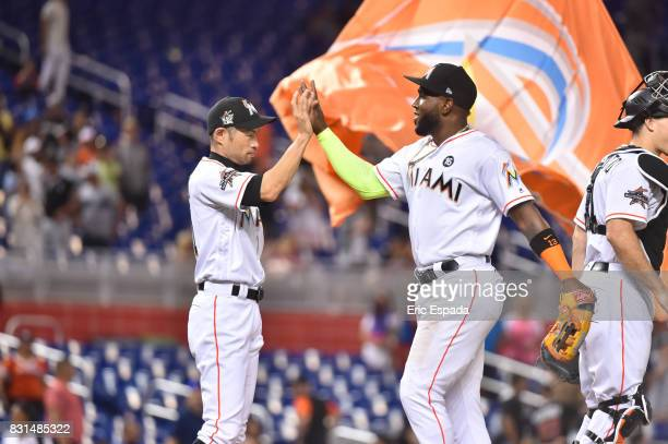 Ichiro Suzuki of the Miami Marlins congratulates Marcell Ozuna after they defeated the San Francisco Giants at Marlins Park on August 14 2017 in...