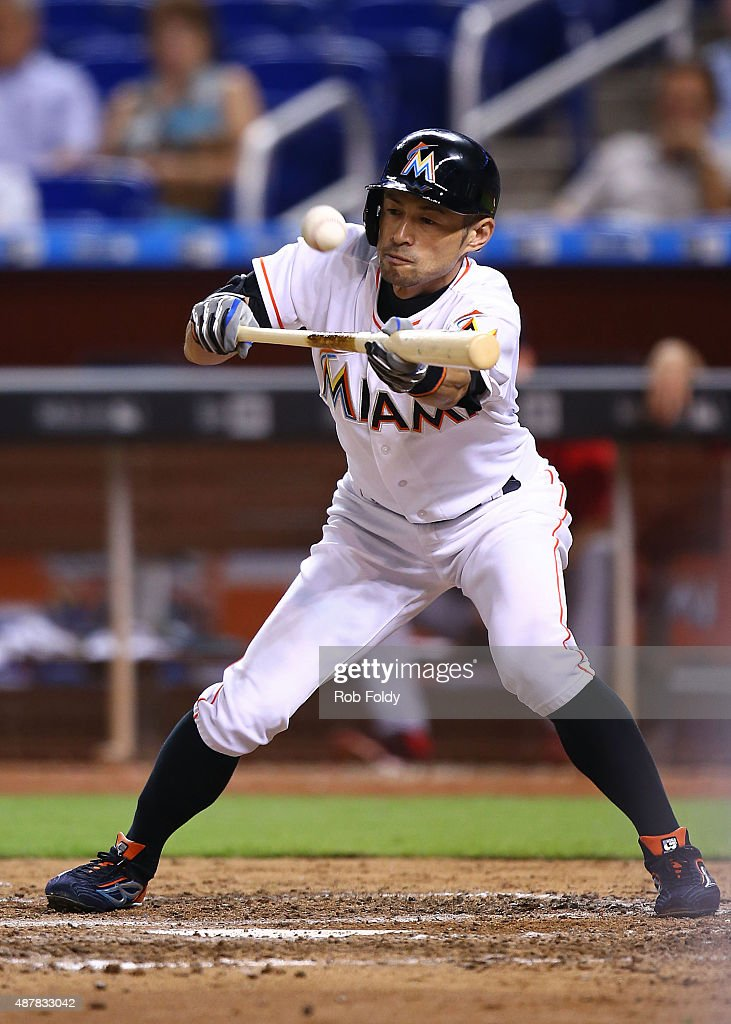 Ichiro Suzuki of the Miami Marlins hits a bunt single to advance JT Realmuto to third base during the seventh inning of the game against the...