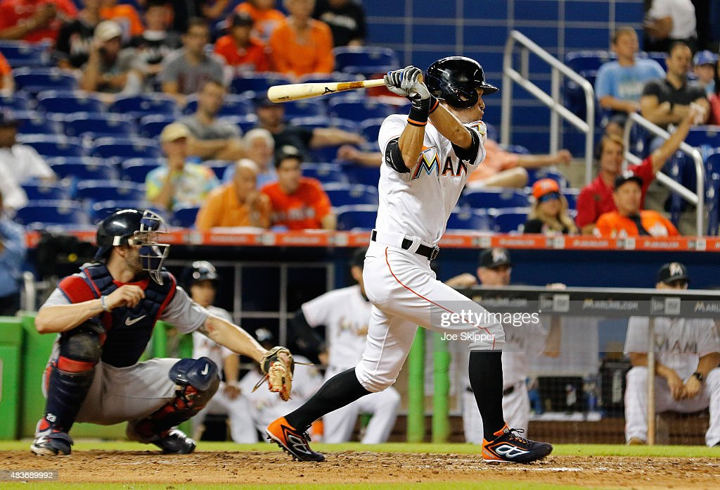 Ichiro Suzuki #51 of the Miami Marlins hits a ninth inning single in front catcher Blake Swihart #23 of the Boston Red Sox at Marlins Park on August 11, 2015 in Miami, Florida.The Marlins won the game 5-4.
