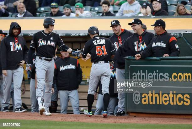 Ichiro Suzuki of the Miami Marlins is congratulated by teammates after he scored in the second inning against the Oakland Athletics at Oakland...