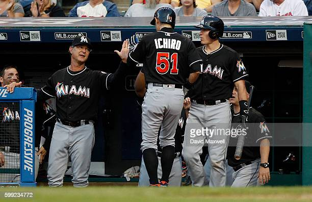 Ichiro Suzuki of the Miami Marlins is greeted as he returns to the dugout after scoring against the Cleveland Indians in the ninth inning of their...