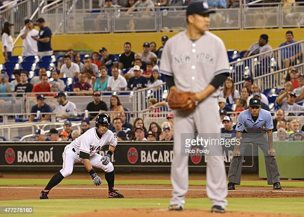 Ichiro Suzuki of the Miami Marlins leads off first base as Masahiro Tanaka of the New York Yankees sets to pitch during the first inning of the game...