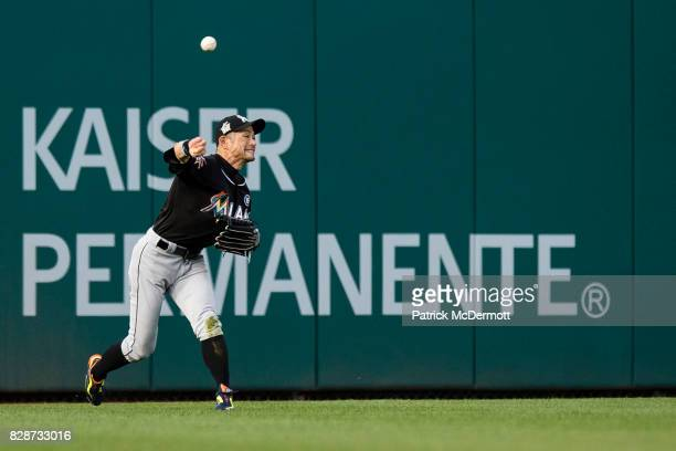 Ichiro Suzuki of the Miami Marlins makes a throw after fielding a single hit by Wilmer Difo of the Washington Nationals in the second inning during a...