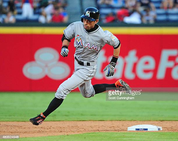 Ichiro Suzuki of the Miami Marlins rounds second base for a ninth inning triple against the Atlanta Braves at Turner Field on August 9 2015 in...