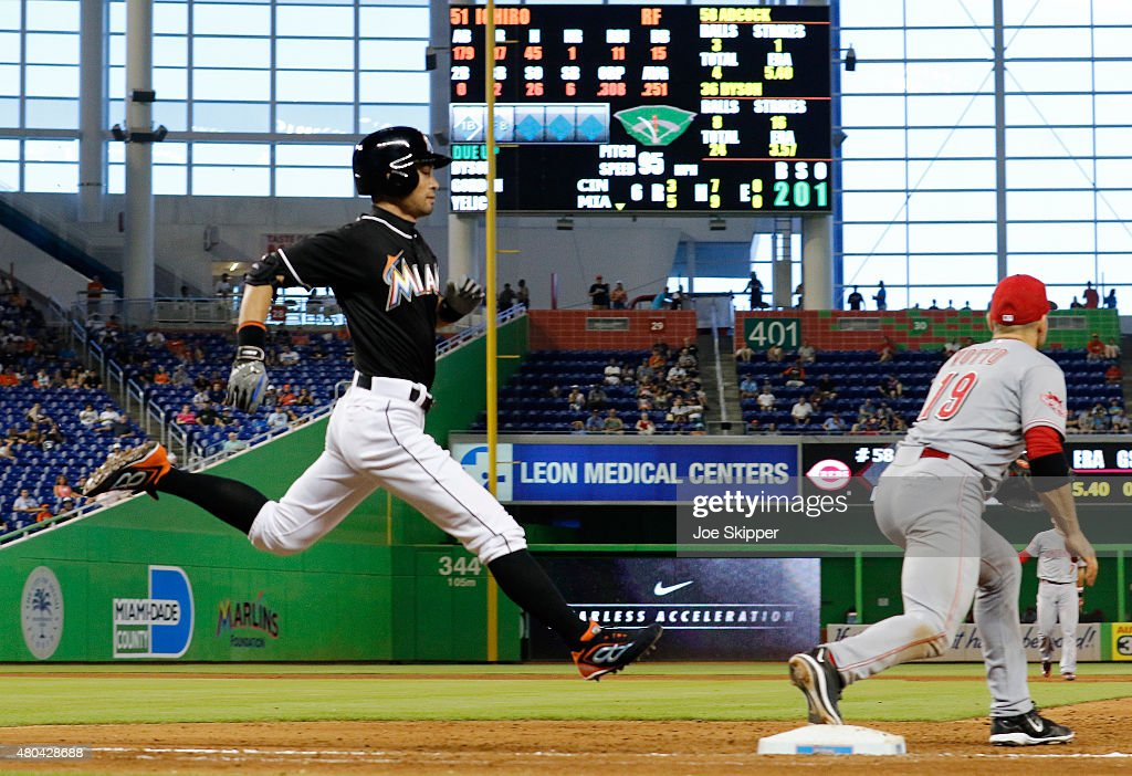 Ichiro Suzuki of the Miami Marlins runs to first base but fails to beat the throw to first baseman Joey Votto of the Cincinnati Reds at Marlins Park...
