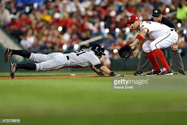 Ichiro Suzuki of the Miami Marlins slides back into first base in the second inning as Ryan Zimmerman of the Washington Nationals stands on the base...