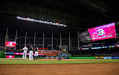Ichiro Suzuki of the Miami Marlins stands on first base with first base coach Perry Hill and Tommy Joseph of the Philadelphia Phillies after getting...