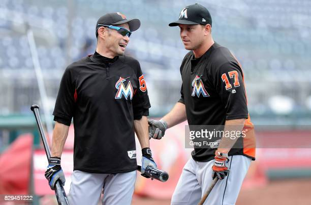 Ichiro Suzuki of the Miami Marlins talks with AJ Ellis before the game against the Washington Nationals at Nationals Park on August 10 2017 in...