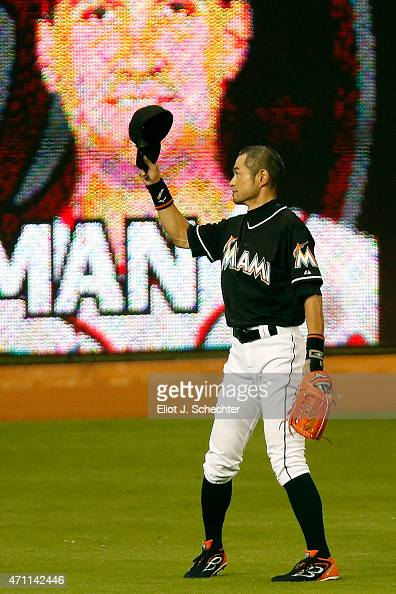 Ichiro Suzuki of the Miami Marlins tips his hat to the crowd after it is announced that he has broken the record for the most runs scored by a...