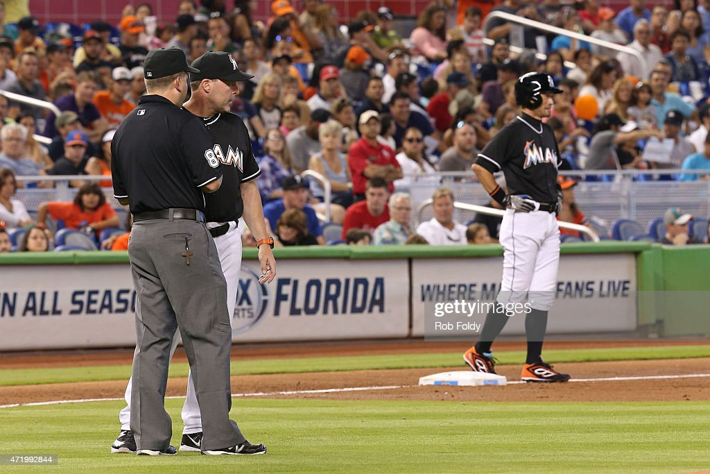 Ichiro Suzuki #51 of the Miami Marlins waits on third base as manager Mike Redmond #11 talks with an umpire after Ichiro was called out at second base during the second inning of the game against the Philadelphia Phillies at Marlins Park on May 2, 2015 in Miami, Florida.
