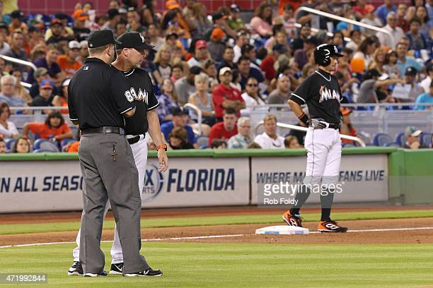 Ichiro Suzuki of the Miami Marlins waits on third base as manager Mike Redmond talks with an umpire after Ichiro was called out at second base during...