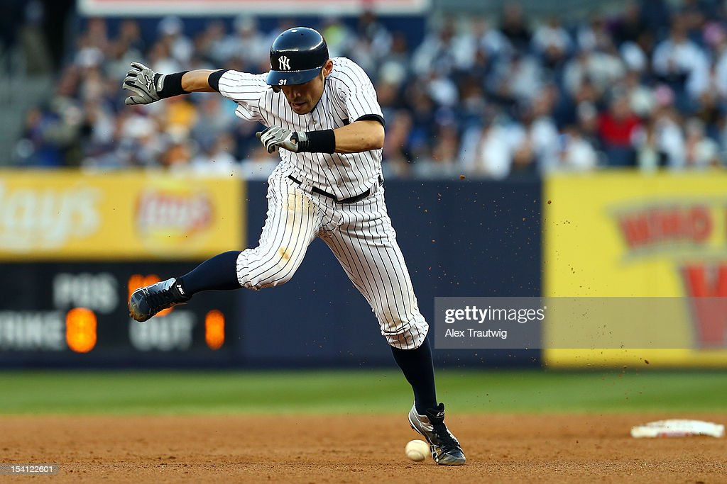 Ichiro Suzuki #31 of the New York Yankees avoids a ground ball hit by Mark Teixeira #25 in the sixth inning against the Detroit Tigers during Game Two of the American League Championship Series at Yankee Stadium on October 14, 2012 in the Bronx borough of New York City.