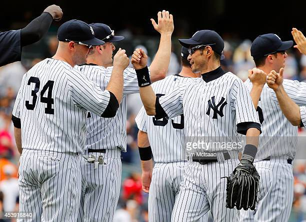 Ichiro Suzuki of the New York Yankees celebrates after defeating the Houston Astros with teammate Brian McCann against the at Yankee Stadium on...