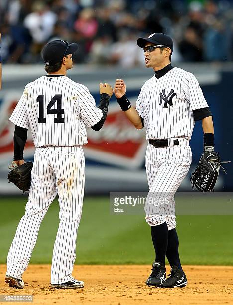 Ichiro Suzuki of the New York Yankees celebrates the win with teammate Brian Roberts after the game against the Los Angeles Angels of Anaheim on...
