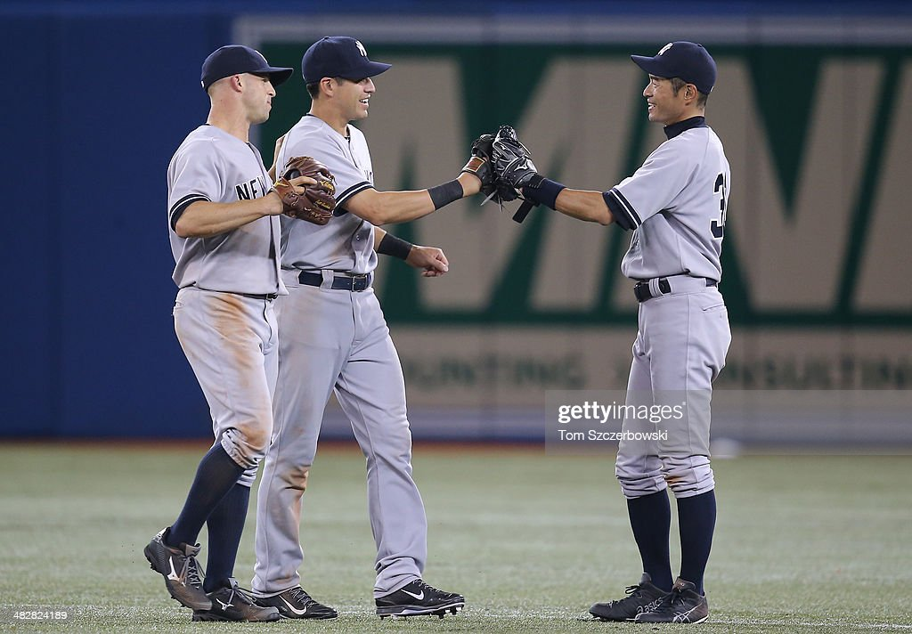 <a gi-track='captionPersonalityLinkClicked' href=/galleries/search?phrase=Ichiro+Suzuki&family=editorial&specificpeople=201556 ng-click='$event.stopPropagation()'>Ichiro Suzuki</a> #31 of the New York Yankees celebrates their victory with <a gi-track='captionPersonalityLinkClicked' href=/galleries/search?phrase=Jacoby+Ellsbury&family=editorial&specificpeople=4172583 ng-click='$event.stopPropagation()'>Jacoby Ellsbury</a> #22 and <a gi-track='captionPersonalityLinkClicked' href=/galleries/search?phrase=Brett+Gardner&family=editorial&specificpeople=4172518 ng-click='$event.stopPropagation()'>Brett Gardner</a> #11 during MLB game action against the Toronto Blue Jays on April 4, 2014 at Rogers Centre in Toronto, Ontario, Canada.