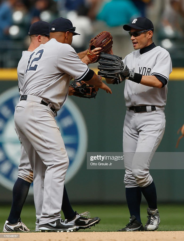 <a gi-track='captionPersonalityLinkClicked' href=/galleries/search?phrase=Ichiro+Suzuki&family=editorial&specificpeople=201556 ng-click='$event.stopPropagation()'>Ichiro Suzuki</a> #31 (R) of the New York Yankees celebrates with <a gi-track='captionPersonalityLinkClicked' href=/galleries/search?phrase=Brett+Gardner&family=editorial&specificpeople=4172518 ng-click='$event.stopPropagation()'>Brett Gardner</a> #11 and Vernon Wells #12 after defeating the Seattle Mariners 2-1 at Safeco Field on June 9, 2013 in Seattle, Washington.