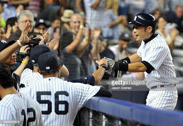Ichiro Suzuki of the New York Yankees celebrates with his teammates after he connects on a solo home run in the fourth inning against the Boston Red...