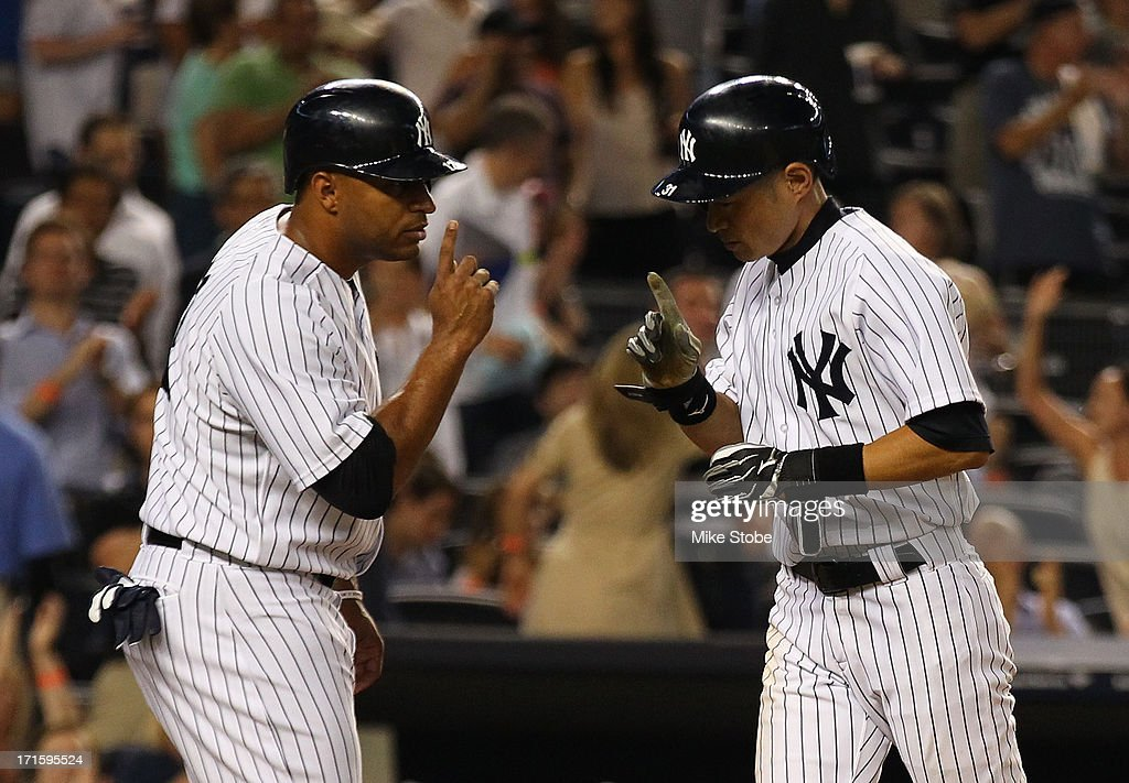 <a gi-track='captionPersonalityLinkClicked' href=/galleries/search?phrase=Ichiro+Suzuki&family=editorial&specificpeople=201556 ng-click='$event.stopPropagation()'>Ichiro Suzuki</a> #31 of the New York Yankees celebrates with teammate <a gi-track='captionPersonalityLinkClicked' href=/galleries/search?phrase=Vernon+Wells&family=editorial&specificpeople=212943 ng-click='$event.stopPropagation()'>Vernon Wells</a> #12 after hitting a two run home run in the seventh inning against the Texas Rangers at Yankee Stadium on June 26, 2013 in the Bronx borough of New York City.