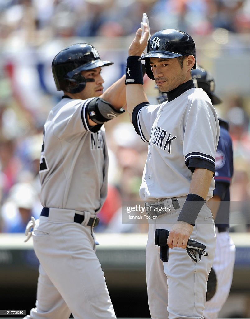 Ichiro Suzuki of the New York Yankees congratulates teammate Jacoby Ellsbury on threerun home run against the Minnesota Twins during the second...