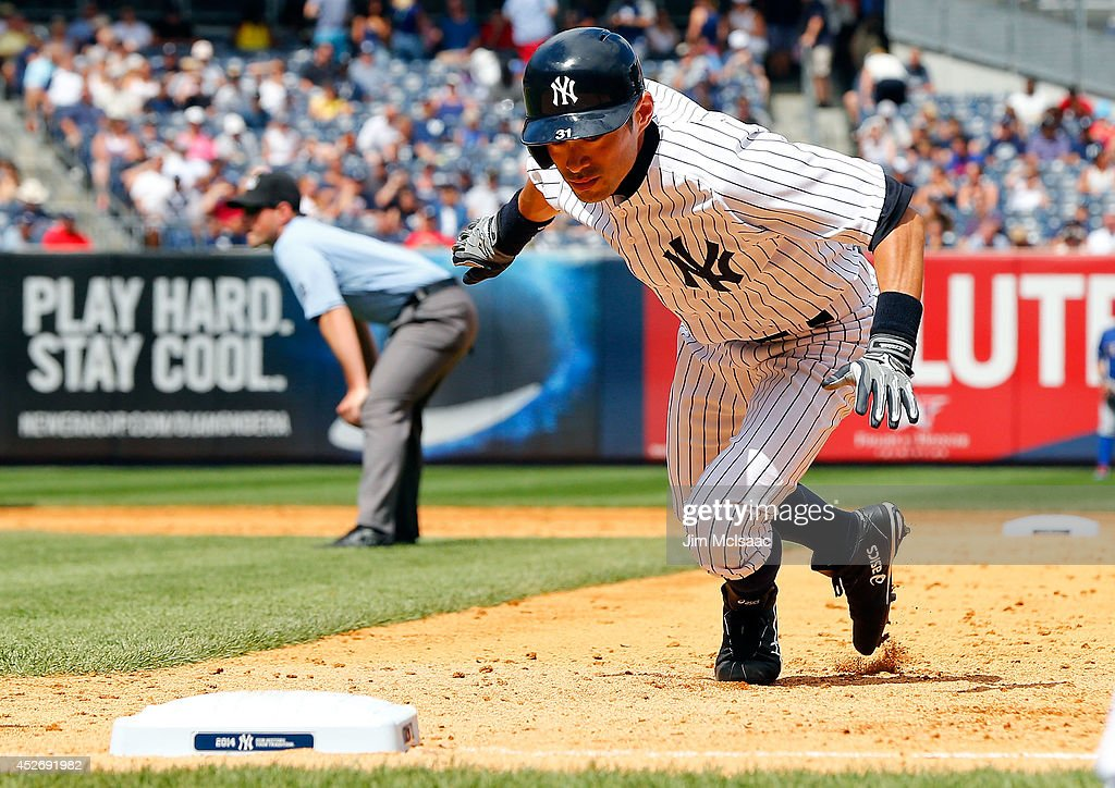 Ichiro Suzuki #31 of the New York Yankees dives back to first base in the sixth inning against the Texas Rangers at Yankee Stadium on July 24, 2014 in the Bronx borough of New York City. The Yankees defeated the Rangers 4-2.