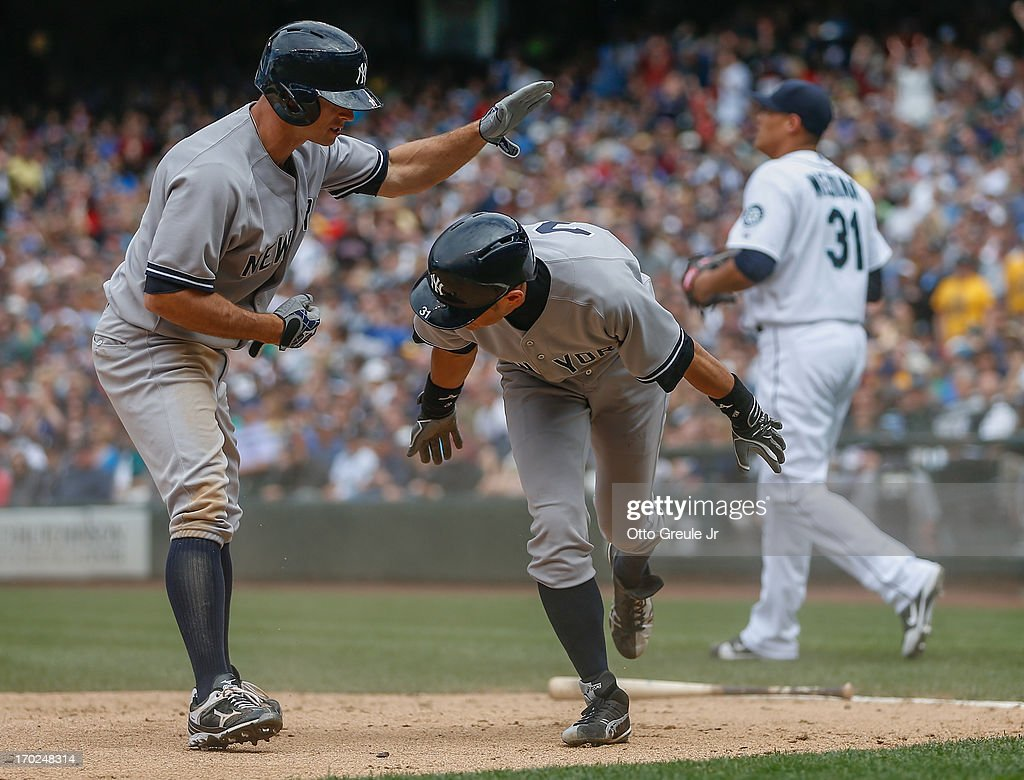 <a gi-track='captionPersonalityLinkClicked' href=/galleries/search?phrase=Ichiro+Suzuki&family=editorial&specificpeople=201556 ng-click='$event.stopPropagation()'>Ichiro Suzuki</a> #31 (C) of the New York Yankees gets a pat on the back from <a gi-track='captionPersonalityLinkClicked' href=/galleries/search?phrase=Brett+Gardner&family=editorial&specificpeople=4172518 ng-click='$event.stopPropagation()'>Brett Gardner</a> #11 after scoring on an RBI single by Chris Stewart in the ninth inning against the Seattle Mariners at Safeco Field on June 9, 2013 in Seattle, Washington. Relief pitcher Yoervis Medina #31 is at right.