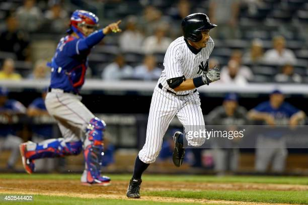 Ichiro Suzuki of the New York Yankees heads for first after he bunted as Robinson Chirinos of the Texas Rangers defends on July 22 2014 at Yankee...