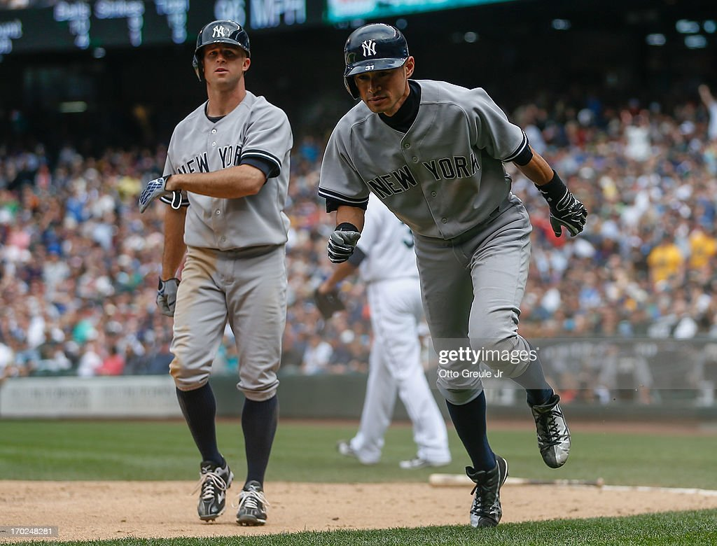 <a gi-track='captionPersonalityLinkClicked' href=/galleries/search?phrase=Ichiro+Suzuki&family=editorial&specificpeople=201556 ng-click='$event.stopPropagation()'>Ichiro Suzuki</a> #31 (R) of the New York Yankees heads into the dugout after scoring on an RBI single by Chris Stewart in the ninth inning against the Seattle Mariners at Safeco Field on June 9, 2013 in Seattle, Washington. Brett Gardner #11 is at left.