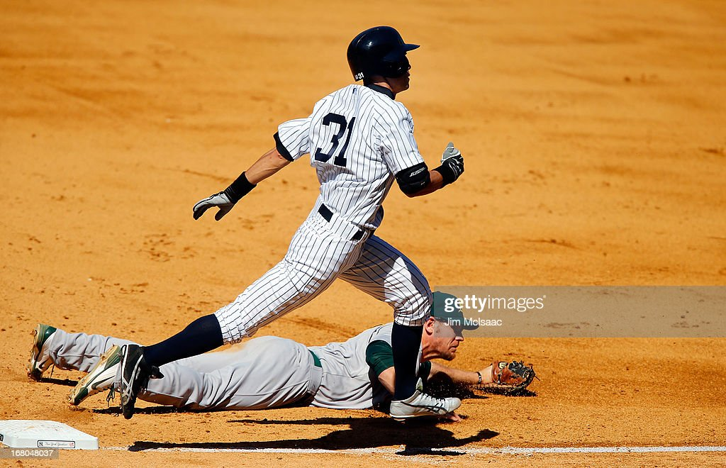 Ichiro Suzuki #31 of the New York Yankees is safe at first after Brandon Moss #37 of the Oakland Athletics can't come up with a ball thrown for an error in the ninth inning at Yankee Stadium on May 4, 2013 in the Bronx borough of New York City.