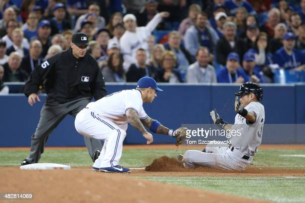 Ichiro Suzuki of the New York Yankees is tagged out in the fifth inning during MLB game action by Brett lawrie of Toronto Blue Jays on April 4 2014...