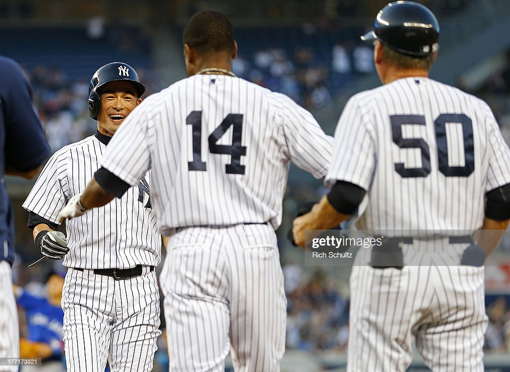 <a gi-track='captionPersonalityLinkClicked' href=/galleries/search?phrase=Ichiro+Suzuki&family=editorial&specificpeople=201556 ng-click='$event.stopPropagation()'>Ichiro Suzuki</a> #31 of the New York Yankees reacts to his teammates including <a gi-track='captionPersonalityLinkClicked' href=/galleries/search?phrase=Curtis+Granderson&family=editorial&specificpeople=546997 ng-click='$event.stopPropagation()'>Curtis Granderson</a> #14 and first base coach <a gi-track='captionPersonalityLinkClicked' href=/galleries/search?phrase=Mick+Kelleher&family=editorial&specificpeople=2496363 ng-click='$event.stopPropagation()'>Mick Kelleher</a> #50 pouring onto the field after hitting a single, his 4,000 career hit, in the first inning against the Toronto Blue Jays in a MLB baseball game at Yankee Stadium on August 21, 2013 in the Bronx borough of New York City.