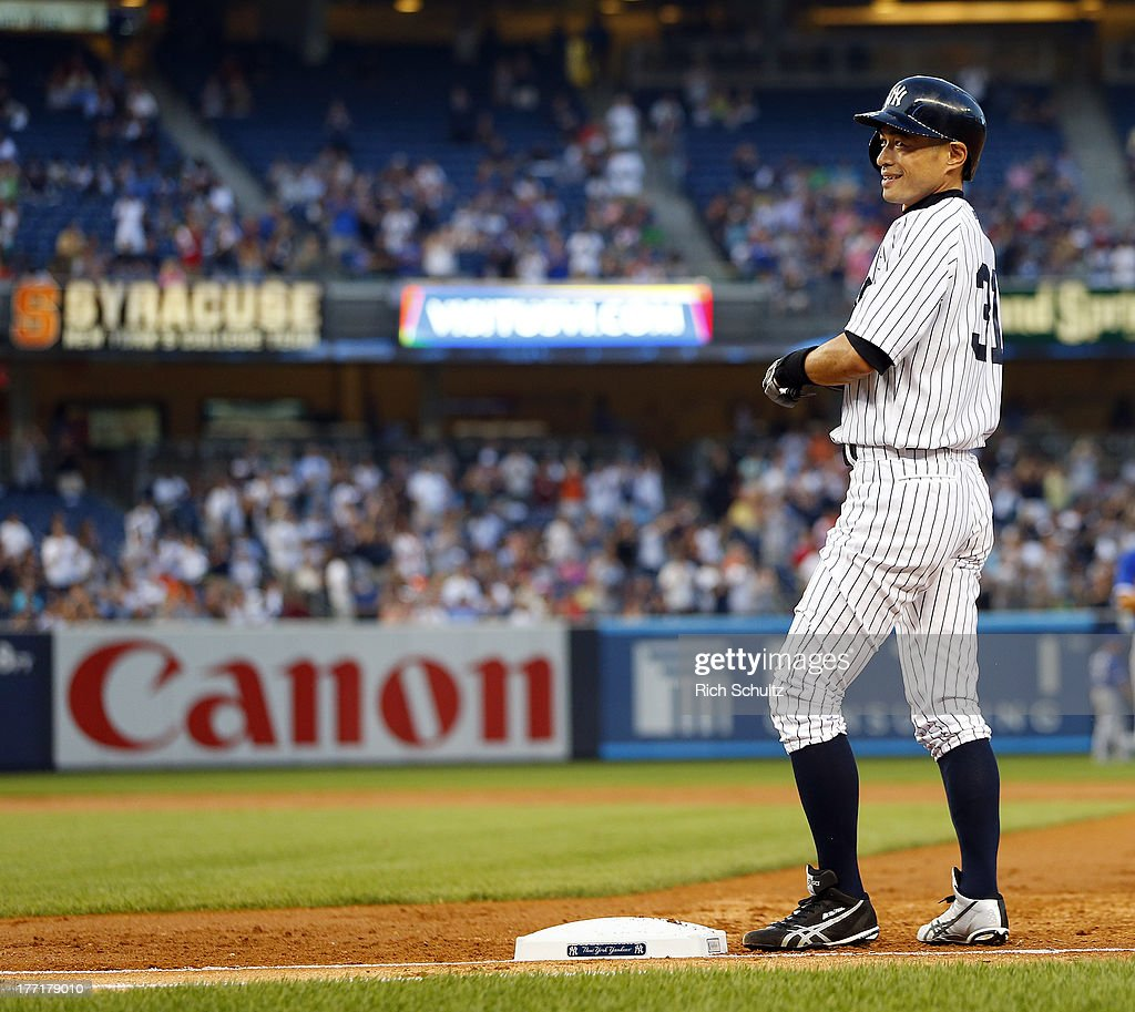 Ichiro Suzuki #31 of the New York Yankees reacts to his teammates pouring onto the field after hitting a single, his 4,000th career hit in the first inning against the Toronto Blue Jays in a MLB baseball game at Yankee Stadium on August 21, 2013 in the Bronx borough of New York City.