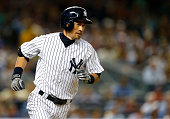 Ichiro Suzuki of the New York Yankees runs to first base as he hits a single in the third inning against the Boston Red Sox during a MLB baseball...