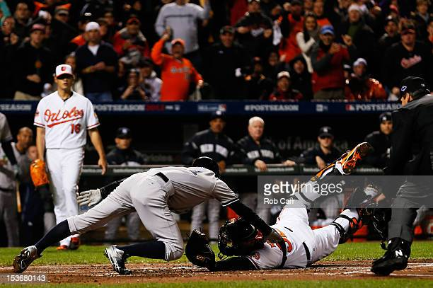 Ichiro Suzuki of the New York Yankees scores a run around catcher Matt Wieters of the Baltimore Orioles on an RBI double hit by Robinson Cano in the...