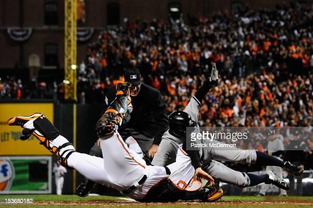 Ichiro Suzuki of the New York Yankees scores a run around catcher Matt Wieters of the Baltimore Orioles on an RBI double hit by Robinson Cano in the...