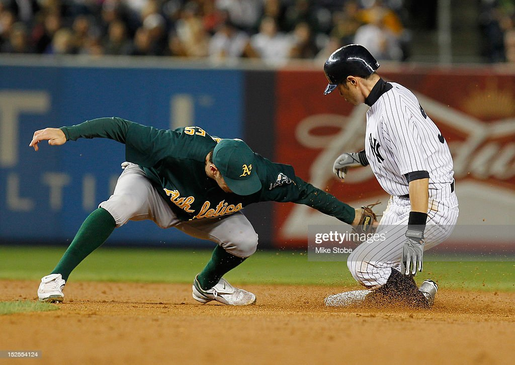 <a gi-track='captionPersonalityLinkClicked' href=/galleries/search?phrase=Ichiro+Suzuki&family=editorial&specificpeople=201556 ng-click='$event.stopPropagation()'>Ichiro Suzuki</a> #31 of the New York Yankees slides in ahead of the tag of <a gi-track='captionPersonalityLinkClicked' href=/galleries/search?phrase=Adam+Rosales&family=editorial&specificpeople=4921731 ng-click='$event.stopPropagation()'>Adam Rosales</a> #17 of the Oakland Athletics for a stolen base in the third inning at Yankee Stadium on September 21, 2012 in the Bronx borough of New York City.