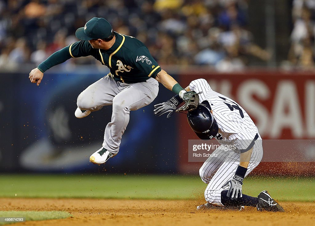 Ichiro Suzuki #31 of the New York Yankees steals second base as the throw gets past second baseman Nick Punto #1 of the Oakland Athletics during the sixth inning in a MLB baseball game at Yankee Stadium on June 4, 2014 in the Bronx borough of New York City.
