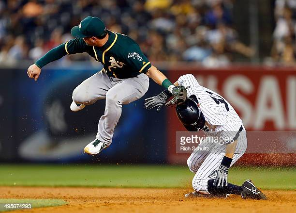 Ichiro Suzuki of the New York Yankees steals second base as the throw gets past second baseman Nick Punto of the Oakland Athletics during the sixth...