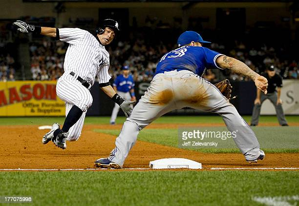 Ichiro Suzuki of the New York Yankees steals third base ahead of a throw to Brett Lawrie of the Toronto Blue Jays during the second game of a double...