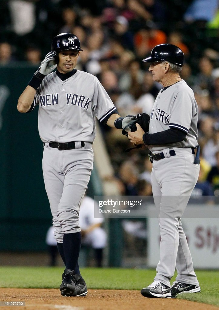 Ichiro Suzuki #31 of the New York Yankees talks with first base coach Mick Kelleher #50 after hitting a single against the Detroit Tigers during the ninth inning at Comerica Park on August 27, 2014 in Detroit, Michigan.