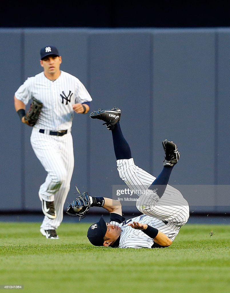 Ichiro Suzuki of the New York Yankees tumbles after making a catch on a ball hit by Stephen Drew of the Boston Red Sox to end the second inning as...