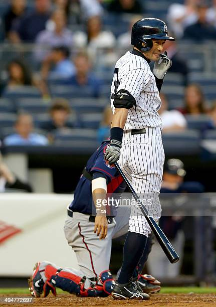 Ichiro Suzuki of the New York Yankees watches as teammate Brian Roberts is nearly picked off at first as Kurt Suzuki of the Minnesota Twins catches...
