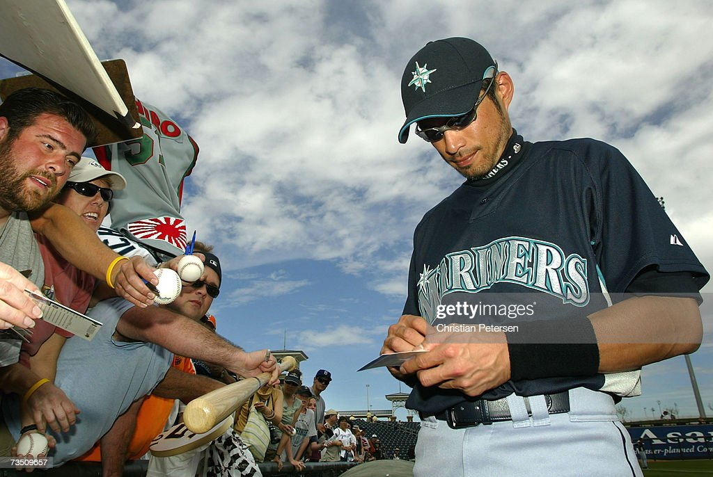 Ichiro Suzuki of the Seattle Mariners signs autographs for fans before the MLB spring training game against the Texas Rangers on March 6 2007 at...