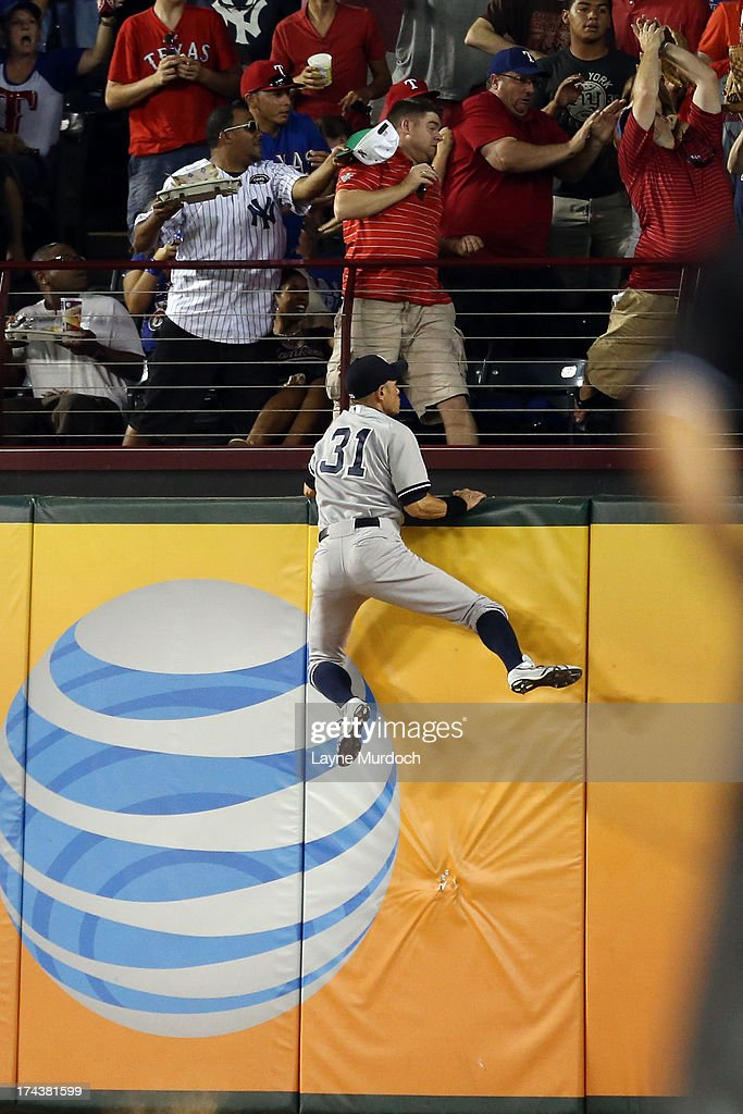 Ichiro Suzuki #31, right fielder for the New York Yankees climbs the wall attempting to catch the home run of A.J. Pierzynski #12 of the Texas Rangers on July 24, 2013 at the Rangers Ballpark in Arlington in Arlington, Texas.