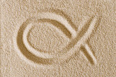Jesus Fish symbol, drawn in sand. Imprint and shape of the ichthys, also ichthus, in ocher grains of sand. The sign consists of two intersecting arcs and resembles the profile of a fish. Macro photo.