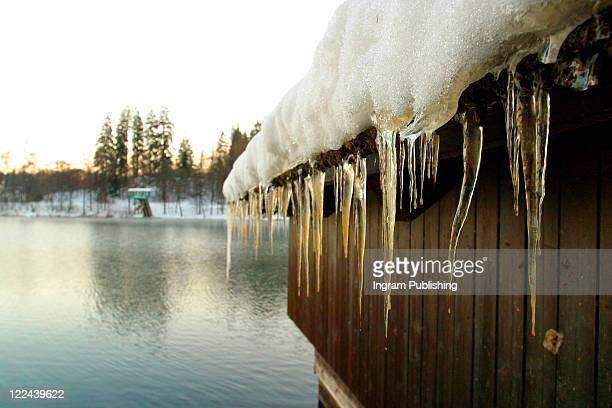 Icicles forming on the roof of a wooden boat shed, Lake Bled, Slovenia.