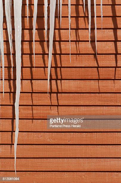 Icicles hang from the eave of a roof and cast shadows on red clapboard siding on a building in Kennebunk on Monday February 16 2015